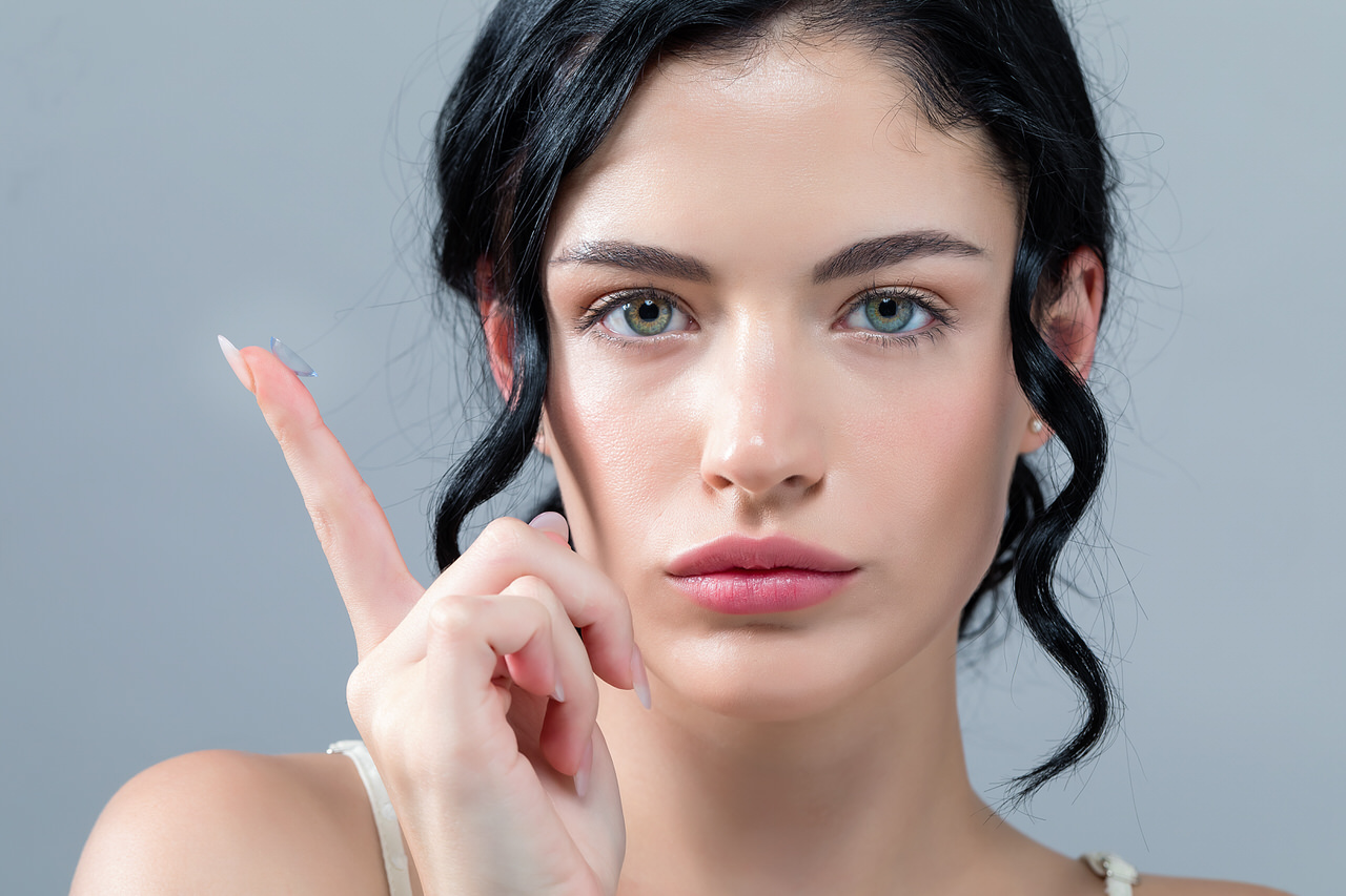 Kontaktlinsen - Frau mit Kontaktlinse auf dem Finger und Strähnen