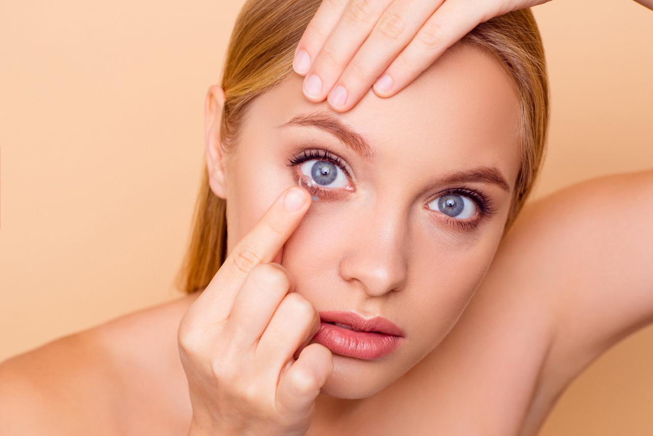 Kontaktlinsen - Frau beim einfügen einer Kontaktlinse