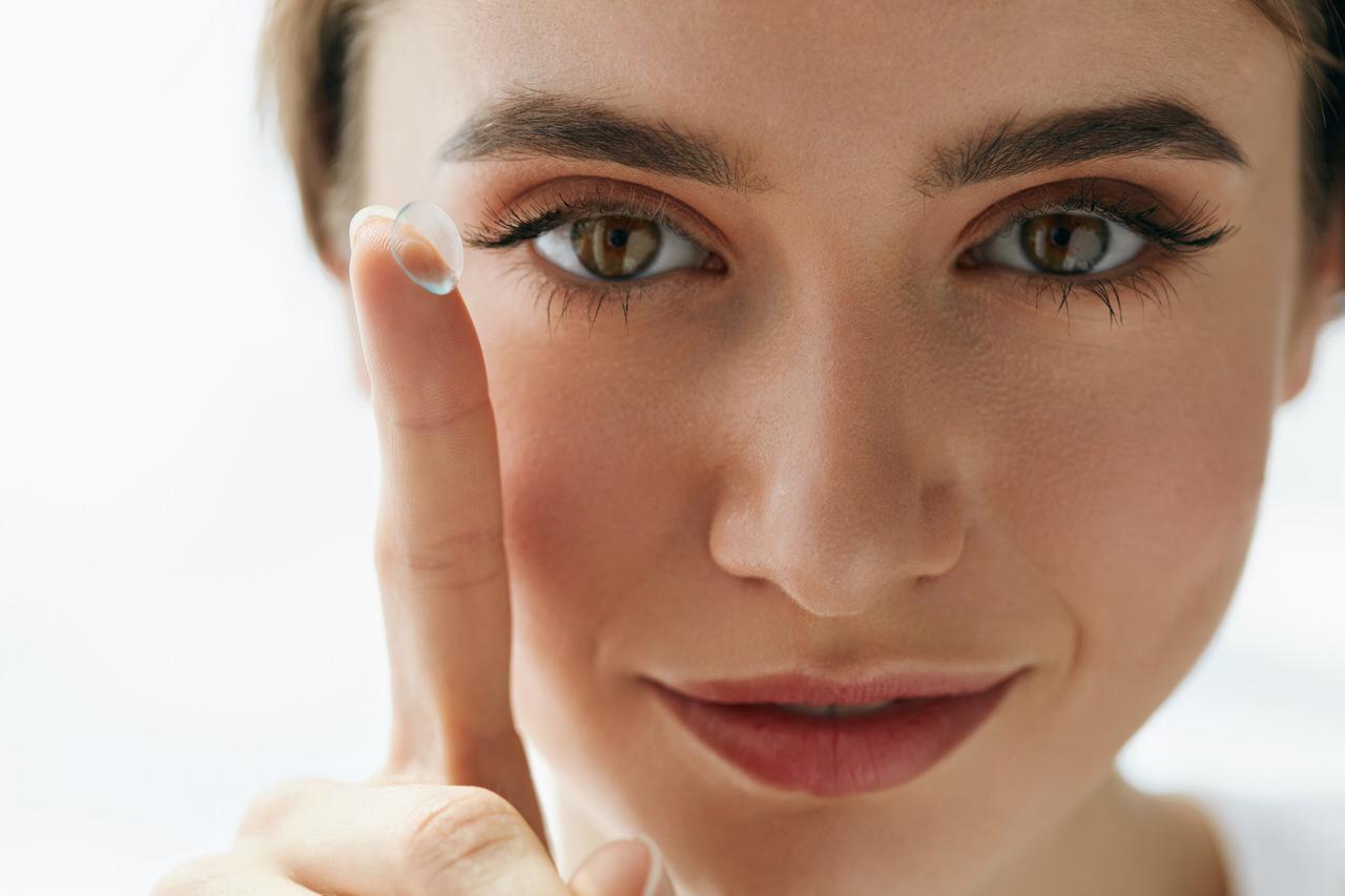 Kontaktlinsen - Nahportrait einer Frau mit Kontaktlinse auf dem Finger