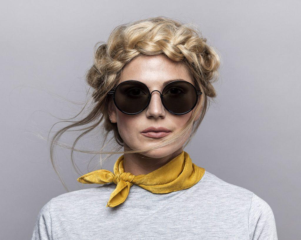 Sonnenbrillen -  Frau mit geflochtenen Haaren und runder Sonnenbrille