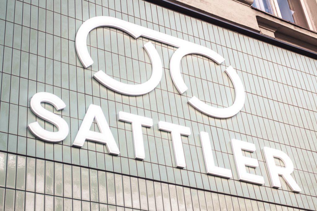 Optiker Wien - Close Up des Firmenlogos auf der Sattler Optik-Filiale auf der Mariahilferstraße in Wien